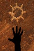 Shadow of hand reaching for sun petroglyph carved into sandstone red rock can Stock Photos