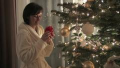 Brunette finding a present under a Christmas tree Stock Footage