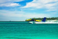 sea plane flying above ocean - stock photo