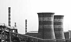 black & white photo of factory with giant chimneys - stock photo