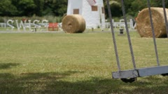 Wooden swing chair at the green field Stock Footage