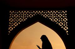 silhoutte of muslim woman praying - stock photo