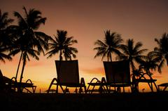row deckchairs on beach at sunset, tanjung aru, malaysia - stock photo