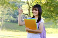 mixed race ok sign college girl standing at campus - stock photo