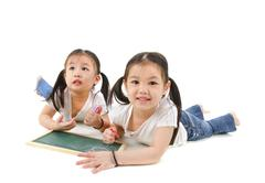 Little asian girl drawing, lying on floor Stock Photos