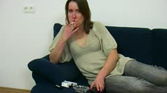 Young woman smokes with a remote control in the hand Stock Footage