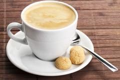 coffee in a white cup with amarettini and spoon - stock photo