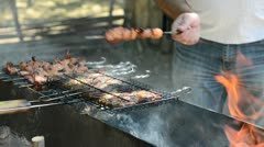 man fries meat on a fire - stock footage