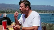 Fast Food Nation - Man Eating Hamburger and French Fries on Sunny Day Stock Footage