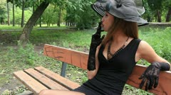 Beautiful girl in a black dress smokes in park Stock Footage