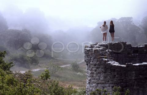 Stock photo of women overlooking bright foggy valley