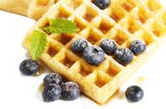 Stock Photo of waffles with sugar covered blueberries and syrup from top