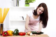 Stock Photo of young happy woman cutting cucumber