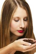 young woman scenting on a handful of coffee beans - stock photo