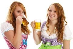 Two bavarian girls laughing and drinking beer Stock Photos