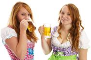 Stock Photo of two bavarian girls laughing and drinking beer