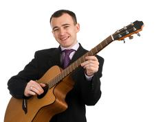 Businessman has a rest playing an acoustic guitar Stock Photos