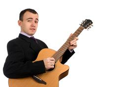 businessman has a rest playing an acoustic guitar - stock photo