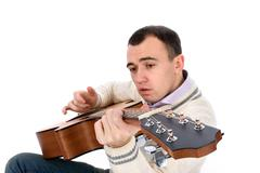 young man playing an acoustic guitar - stock photo