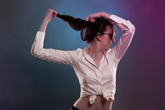 young woman in colorful light pulling her hair - stock photo