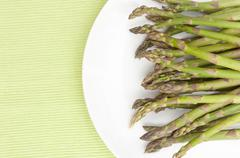 spears of fresh uncooked asparagus on white plate - stock photo