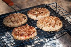 Hamburgers on barbeque grill Stock Photos