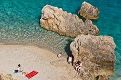 people on the rocky beach in croatia - stock photo