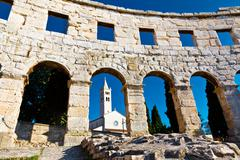 Ancient roman amphitheater and church in pula, istria, croatia Stock Photos