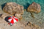 Stock Photo of red and white parasol on the rocky beach in croatia