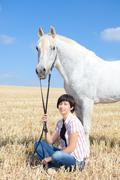 Smiling Young Woman Posing with Her Horse Stock Photos