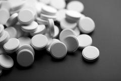 white pills over black background - stock photo