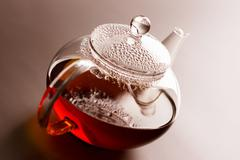 Glass teapot with black tea Stock Photos