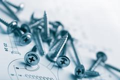 metal screws over technical drawing background - stock photo