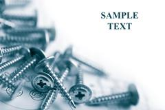 metal screws over technical drawing isolated with copyspace - stock photo