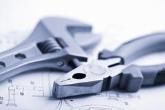 Wrench and pliers over technical drawing toned blue Stock Photos