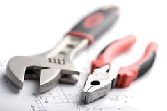 wrench and pliers over technical drawing isolated - stock photo