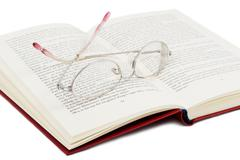 Open book with glasses on it Stock Photos