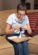 lady jeweller making pendant - stock photo
