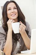 beautiful woman using a computer and drinking tea or coffee - stock photo