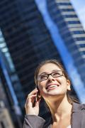 woman or businesswoman talking on cell phone in city - stock photo