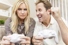 Couple having fun playing video console game Stock Photos
