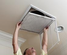 senior man opening air conditioning filter in ceiling - stock photo