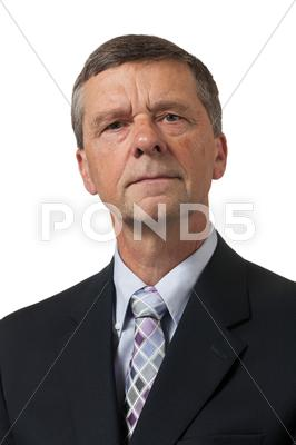 Stock photo of senior man in blue shirt looks pensive