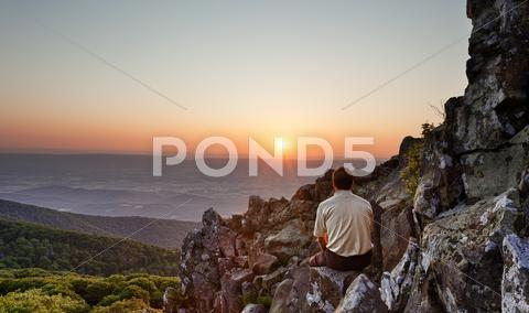 Stock photo of senior man watches sunrise over blue ridge