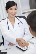 Stock Photo of chinese female woman hospital doctor shaking hands