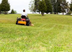senior man on zero turn lawn mower on turf - stock photo