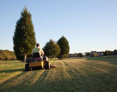 Senior mowing lawn Stock Photos