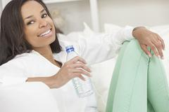 african american woman drinking bottle of water - stock photo