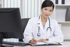 Stock Photo of chinese female woman hospital doctor writing in office