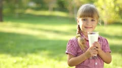 Happy little girl holding a glass of milk Stock Footage